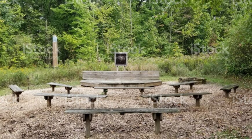 Outdoor classroom with wooden benches and stage surrounded by forest